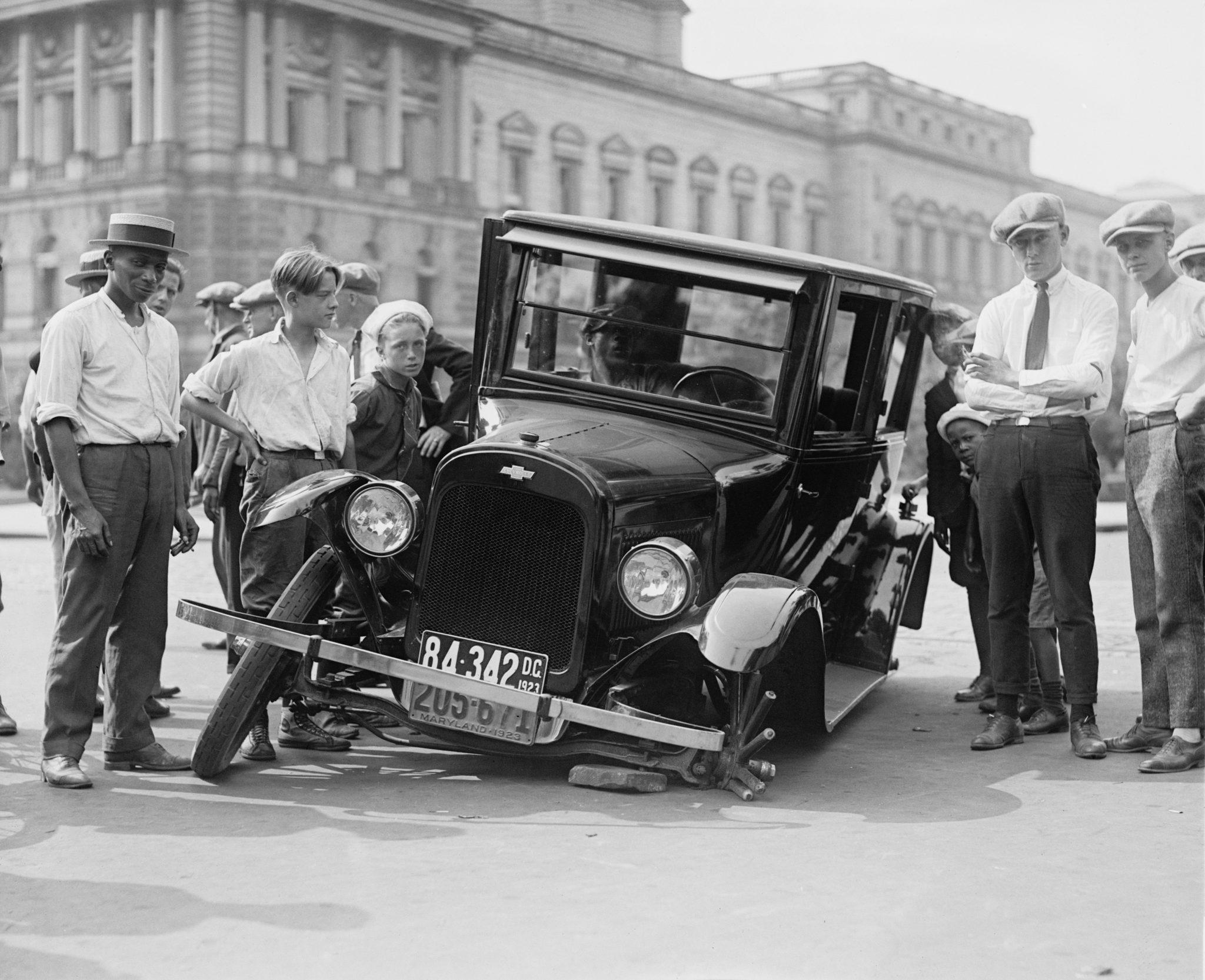 Oude foto met mensen die om een auto staan