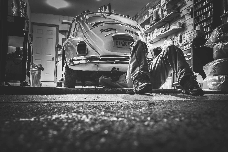 Automonteur ligt onder auto om te repareren