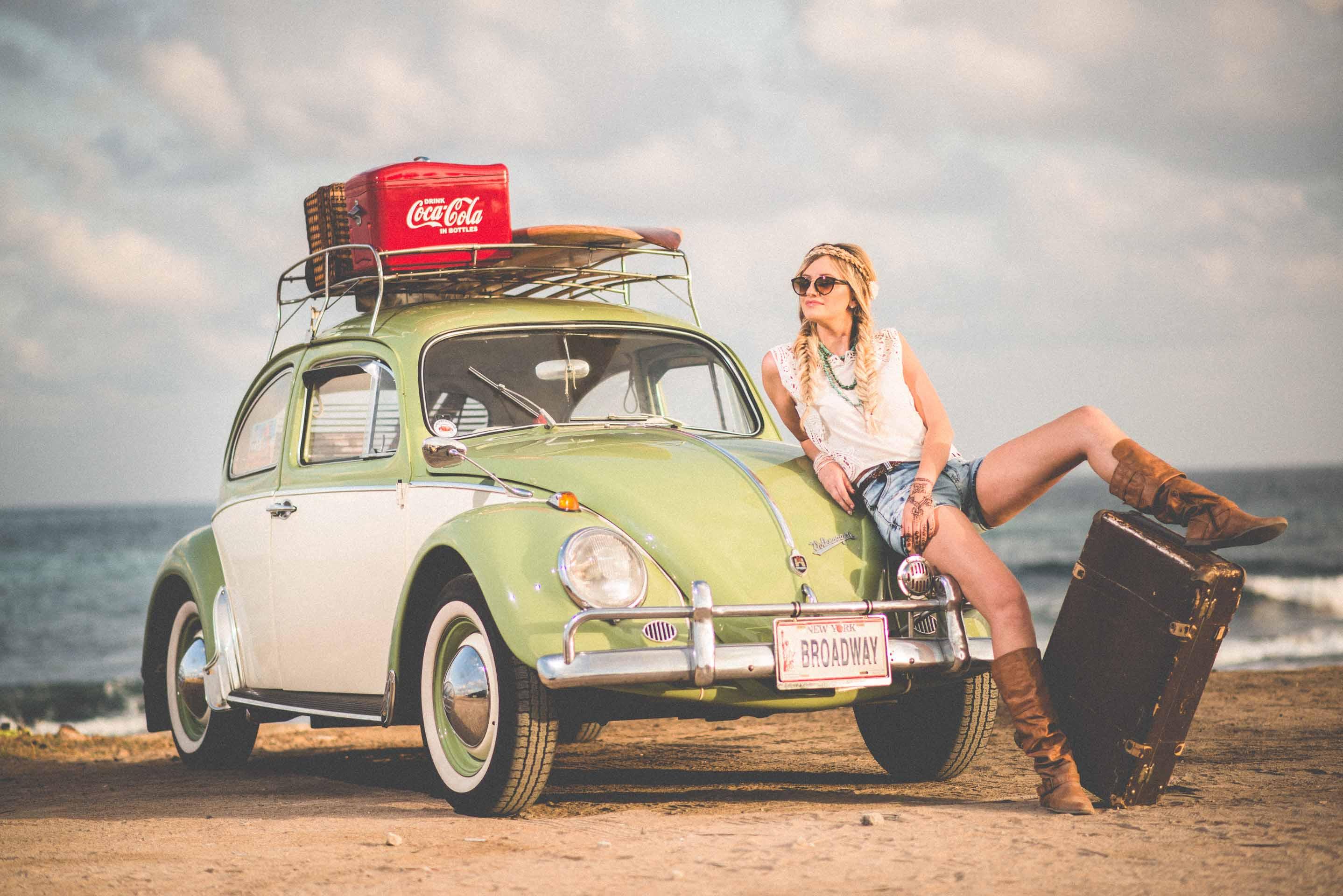 Vrouw leunend tegen vintage auto met koffer