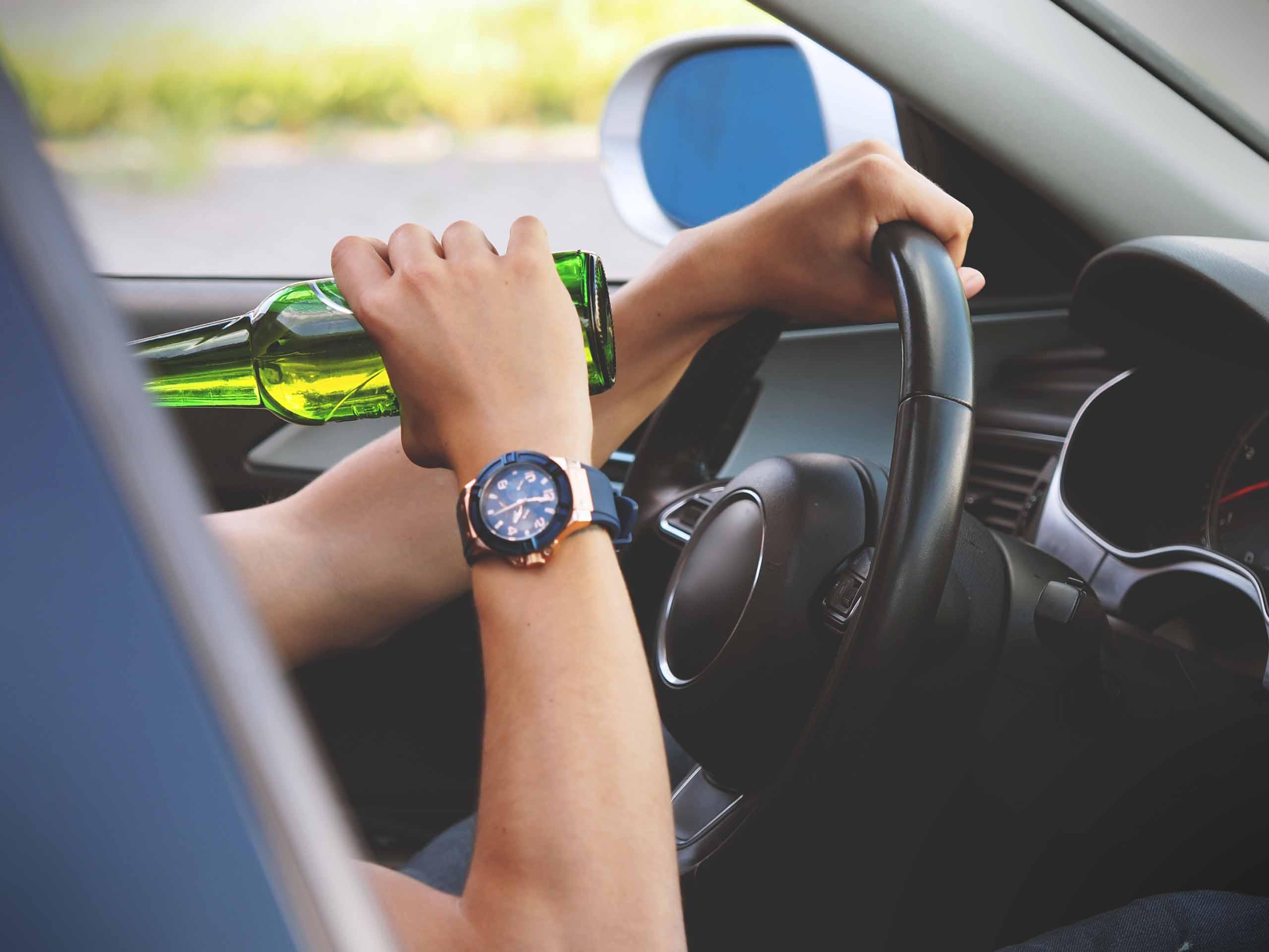 Persoon drinkt achter het stuur