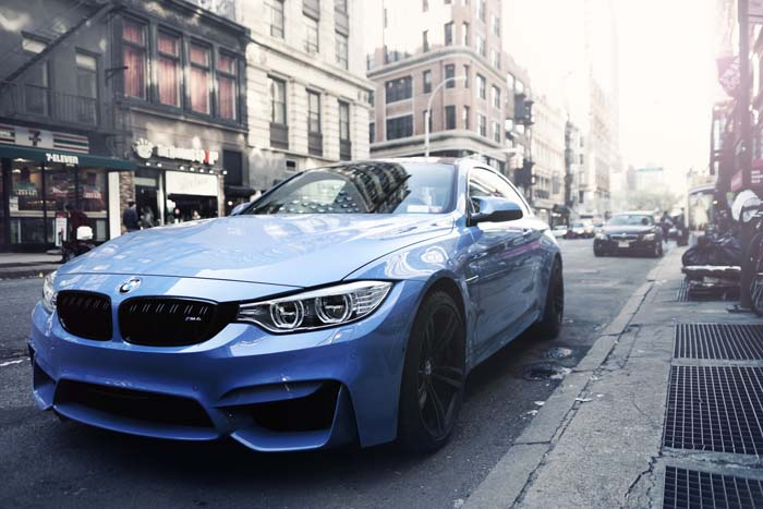 Lichtblauwe BMW geparkeerd langs stoep