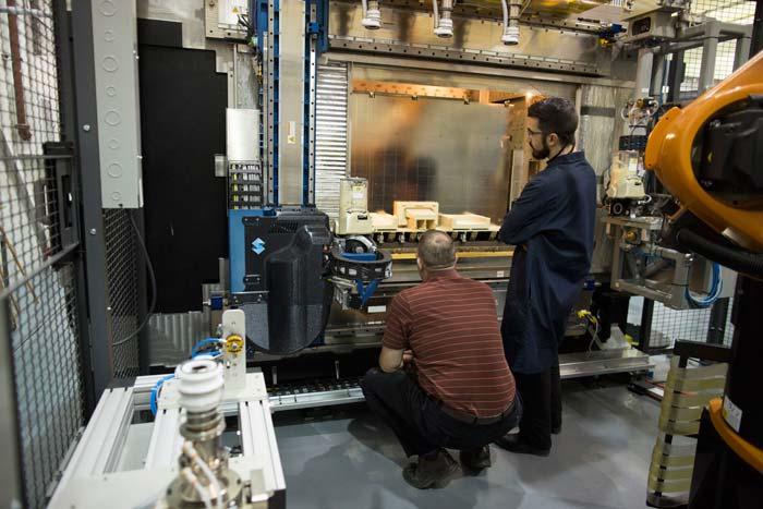 Twee mannen die staan voor een 3D-printer bij Ford