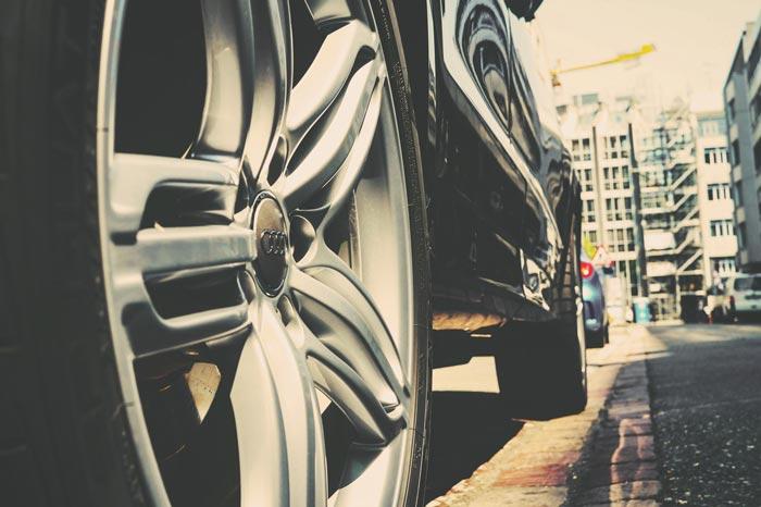Audi ingezoomd op het wiel met gebouwen op achtergrond