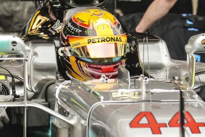 Lewis Hamilton met helm op in formule 1-auto