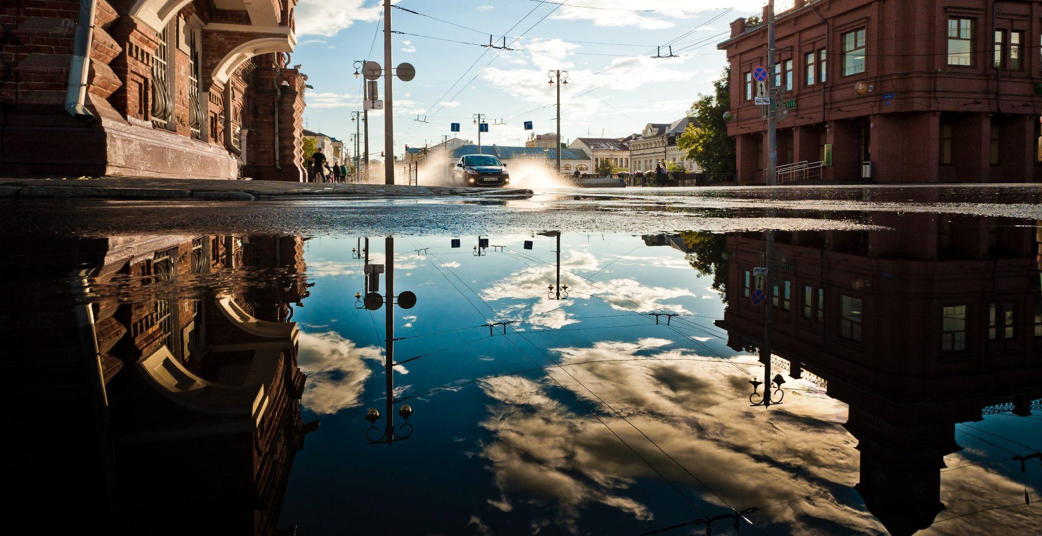 Auto die rijdt door een grote plas water met omgevingweerspiegeling in een plas water