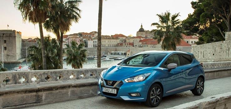 Blauwe Nissan Micra met oude stad op de achtergrond