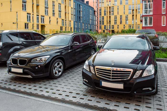 Zwarte Mercedes en BMW naast elkaar op straat