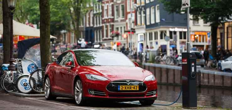 Rode Tesla gekoppeld aan oplaadpunt in Amsterdam