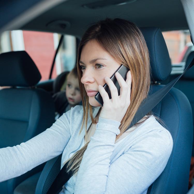 Vrouw in auto aan de telefoon terwijl er een kind achterin zit