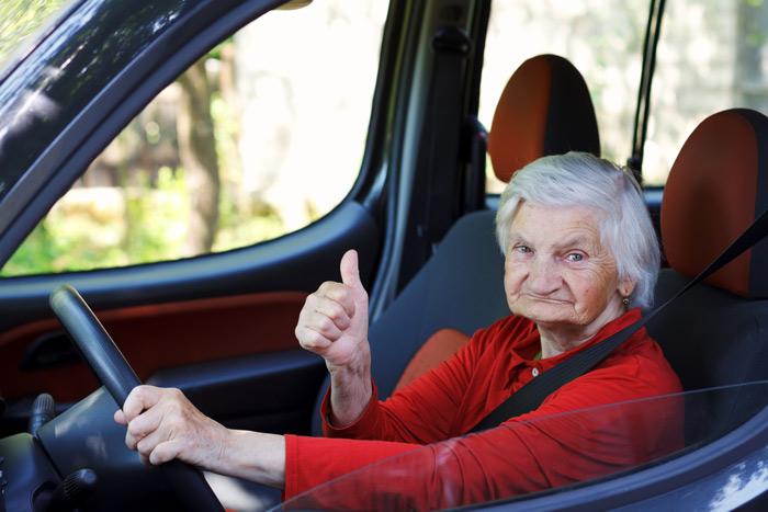 Oude vrouw achter het stuur in auto
